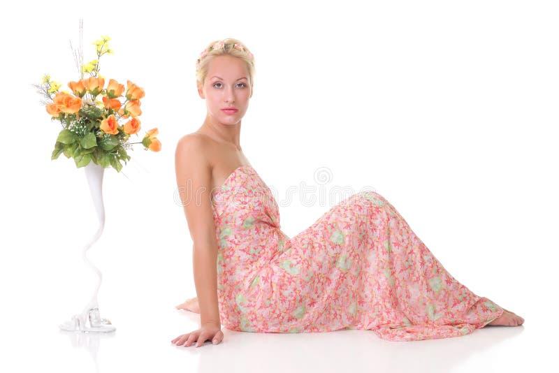 muchacha que se sienta al lado de un florero de flores imagen de archivo