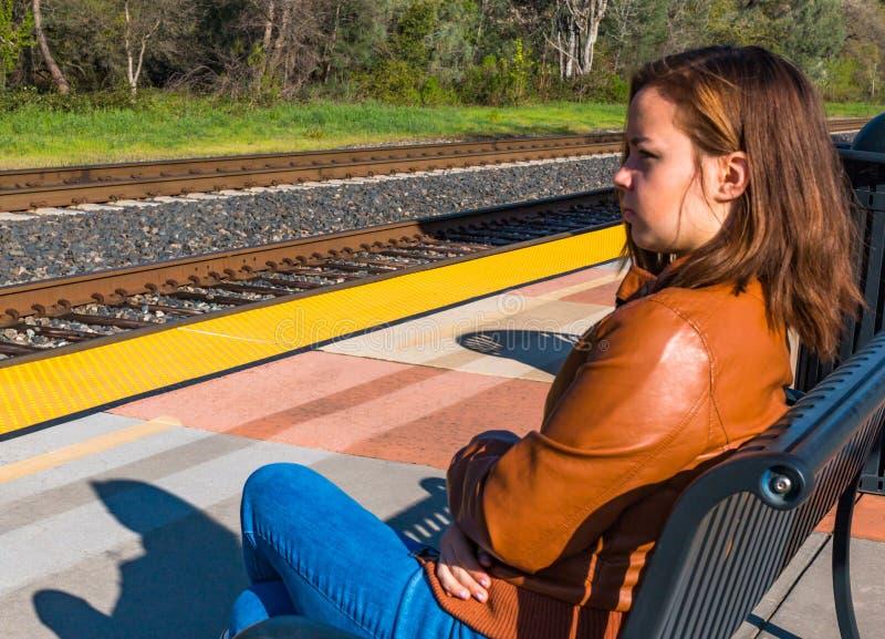 Muchacha que se sienta cerca de los carriles del tren imagen de archivo