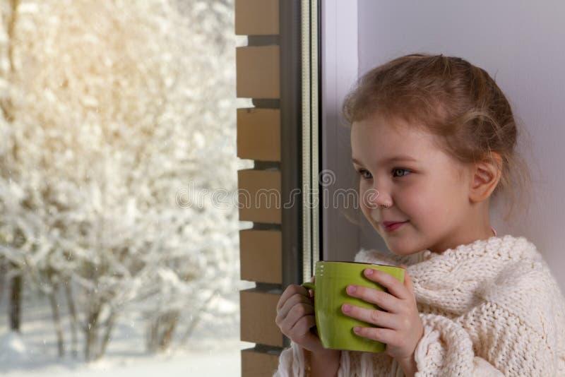 Muchacha que se sienta cerca de ventanas en la casa en el invierno imagen de archivo