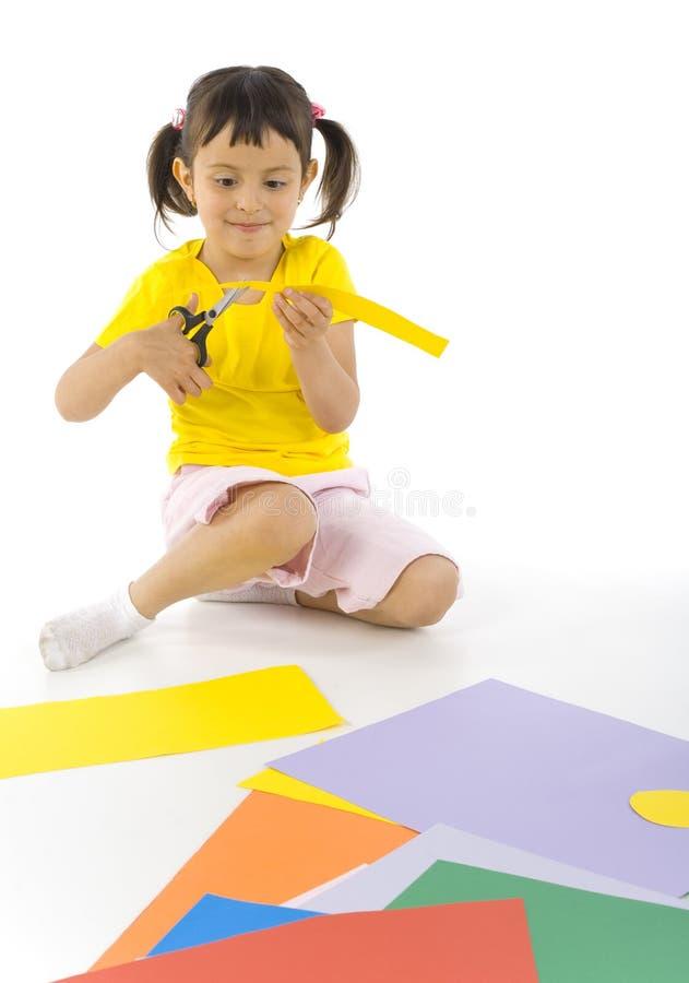 Muchacha que se sienta con las tijeras imagen de archivo