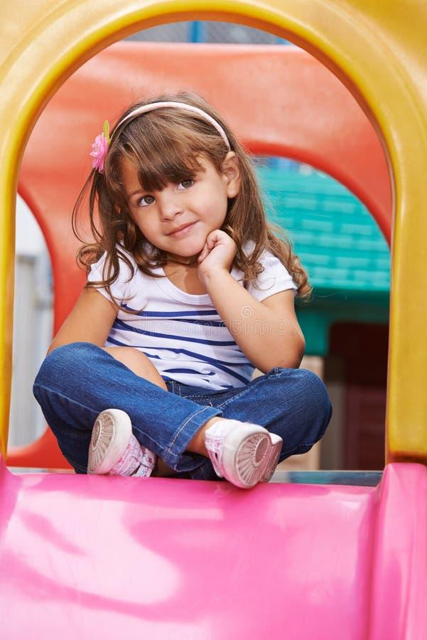 Muchacha que se sienta en asiento del sastre en diapositiva foto de archivo libre de regalías