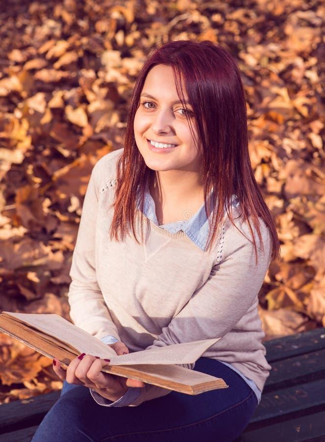 Muchacha que se sienta en banco en arca y que lee un libro foto de archivo