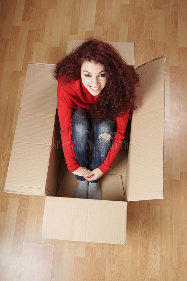 Muchacha que se sienta en caja de cartón imagen de archivo