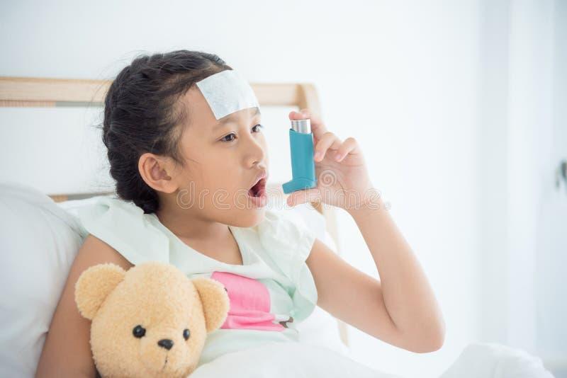 Muchacha que se sienta en cama y que usa el inhalador del broncodilator fotos de archivo