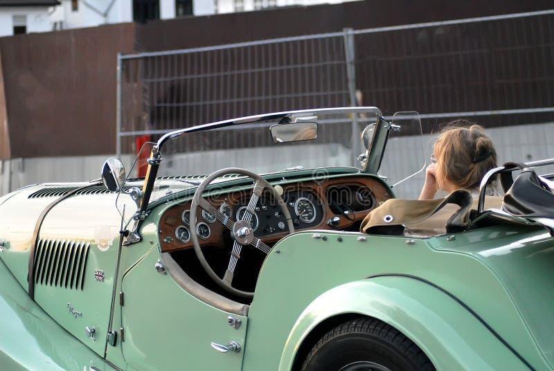 Muchacha que se sienta en coche del vintage fotografía de archivo
