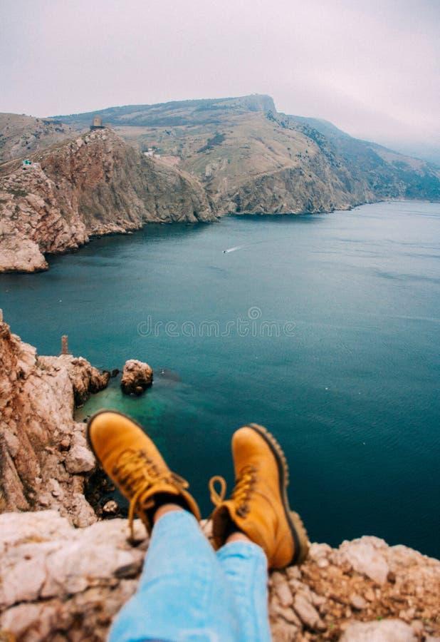 Muchacha que se sienta en el acantilado delante de la fractura sobre el mar imagenes de archivo