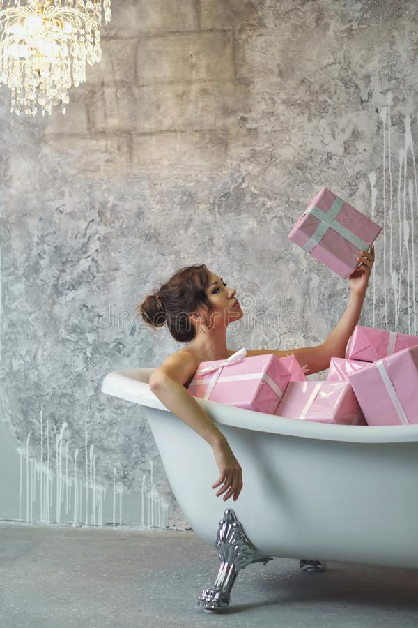 Muchacha que se sienta en el baño con los regalos fotografía de archivo libre de regalías