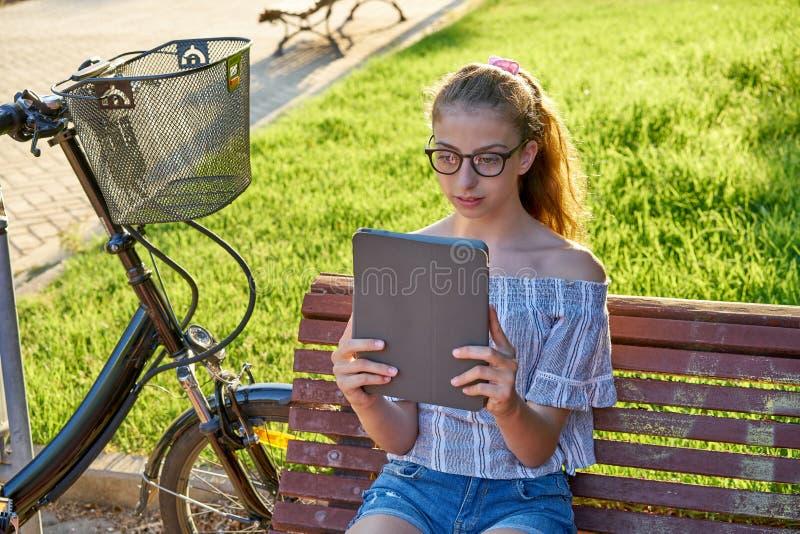 Muchacha que se sienta en el banco de parque que juega con la tableta fotografía de archivo libre de regalías