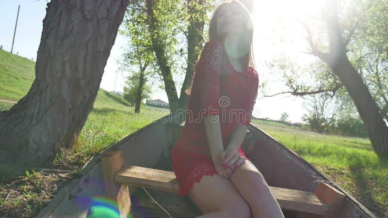 Muchacha que se sienta en el barco viejo mujer joven de la forma de vida en un vestido rojo que se sienta en un barco viejo en el imagen de archivo