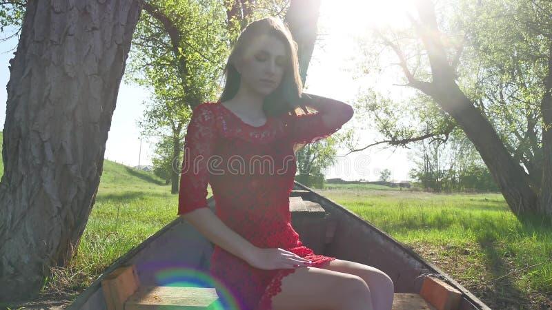 Muchacha que se sienta en el barco viejo mujer joven en un vestido rojo que se sienta en un barco viejo en el río en la forma de  imagen de archivo libre de regalías