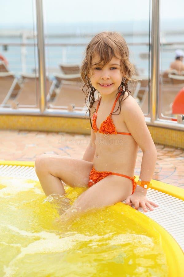 Muchacha que se sienta en el borde de la piscina imagen de archivo