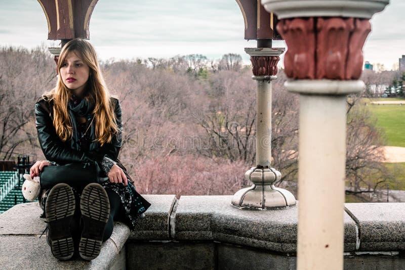 Muchacha que se sienta en el borde del castillo del belvedere en el Central Park en horas-hombre imagen de archivo