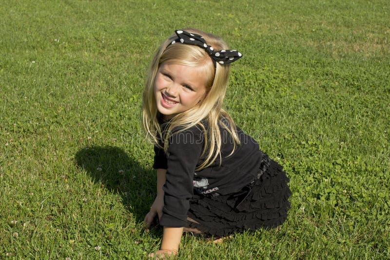Muchacha que se sienta en el césped verde fotografía de archivo libre de regalías