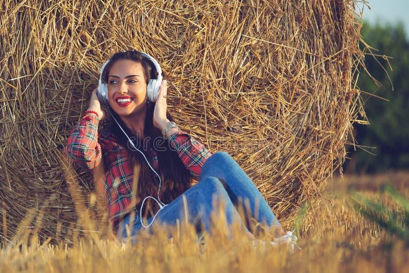 Muchacha que se sienta en el campo de trigo con sus auriculares encendido Ella está inclinando su parte posterior en un pajar foto de archivo