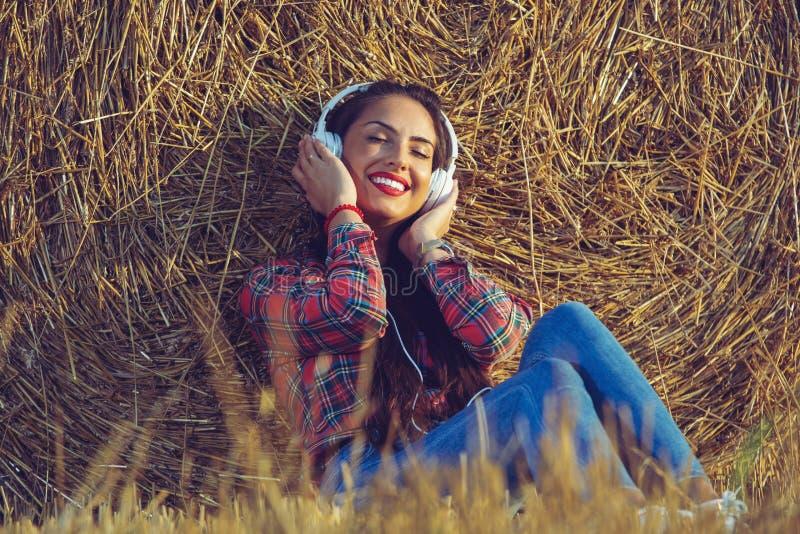 Muchacha que se sienta en el campo de trigo con sus auriculares encendido Ella está inclinando su parte posterior en un pajar fotos de archivo