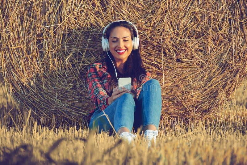 Muchacha que se sienta en el campo de trigo con sus auriculares encendido Ella está inclinando su parte posterior en un pajar imagen de archivo