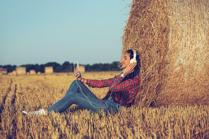 Muchacha que se sienta en el campo de trigo, música que escucha fotografía de archivo