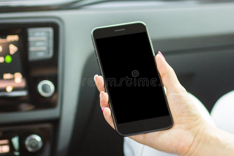 Muchacha que se sienta en el coche que sostiene un smartphone en su mano, primer fotos de archivo libres de regalías