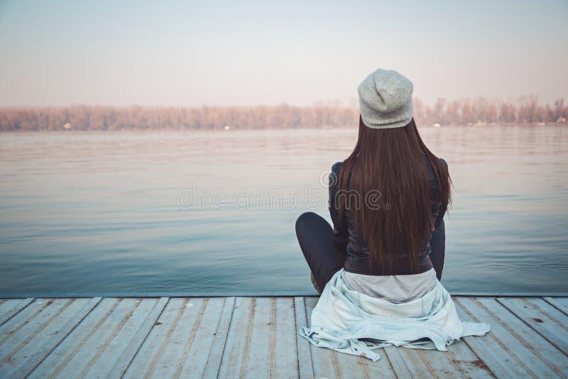 Muchacha que se sienta en el embarcadero y que mira el río fotos de archivo libres de regalías