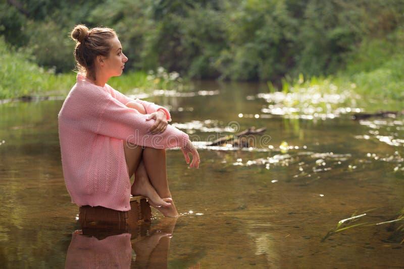 Muchacha que se sienta en el medio del río del bosque imagenes de archivo