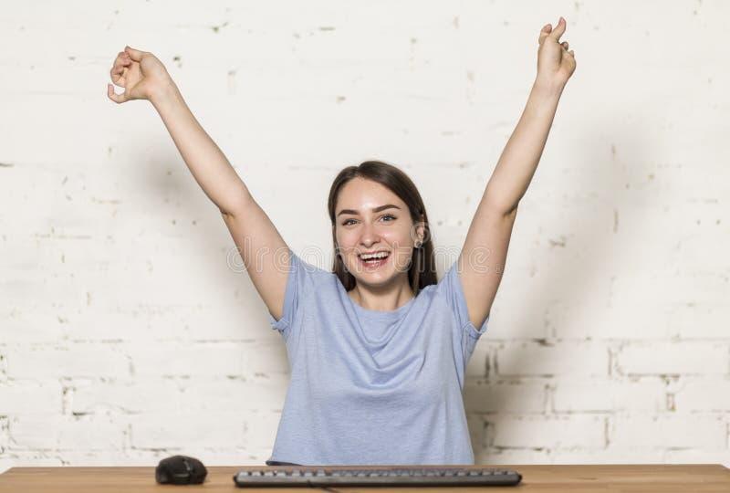 Muchacha que se sienta en el ordenador Ella aumentó sus manos encima de la colina y sonrió En la tabla hay un teclado y un ratón foto de archivo libre de regalías