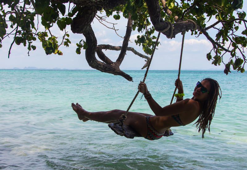 Muchacha que se sienta en el oscilación, playa tropical fotos de archivo
