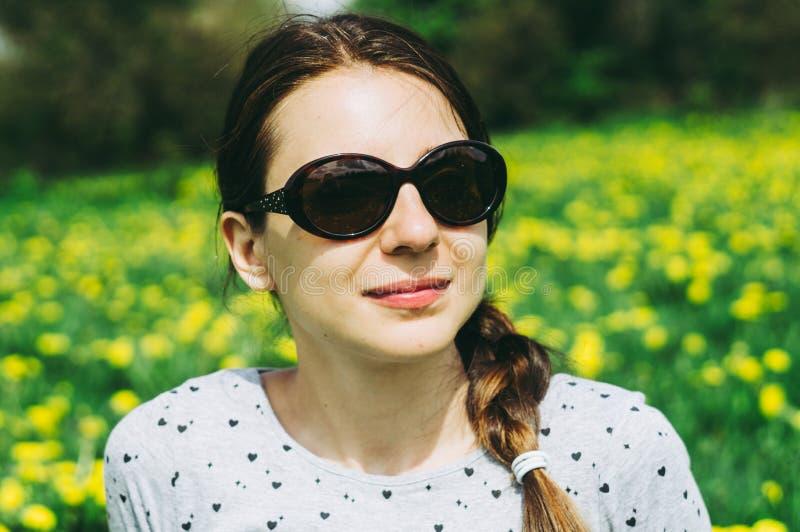 Muchacha que se sienta en el prado con los dientes de le?n amarillos fotografía de archivo