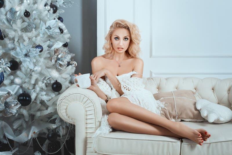 Muchacha que se sienta en el sofá blanco con la taza en sus manos fotografía de archivo libre de regalías