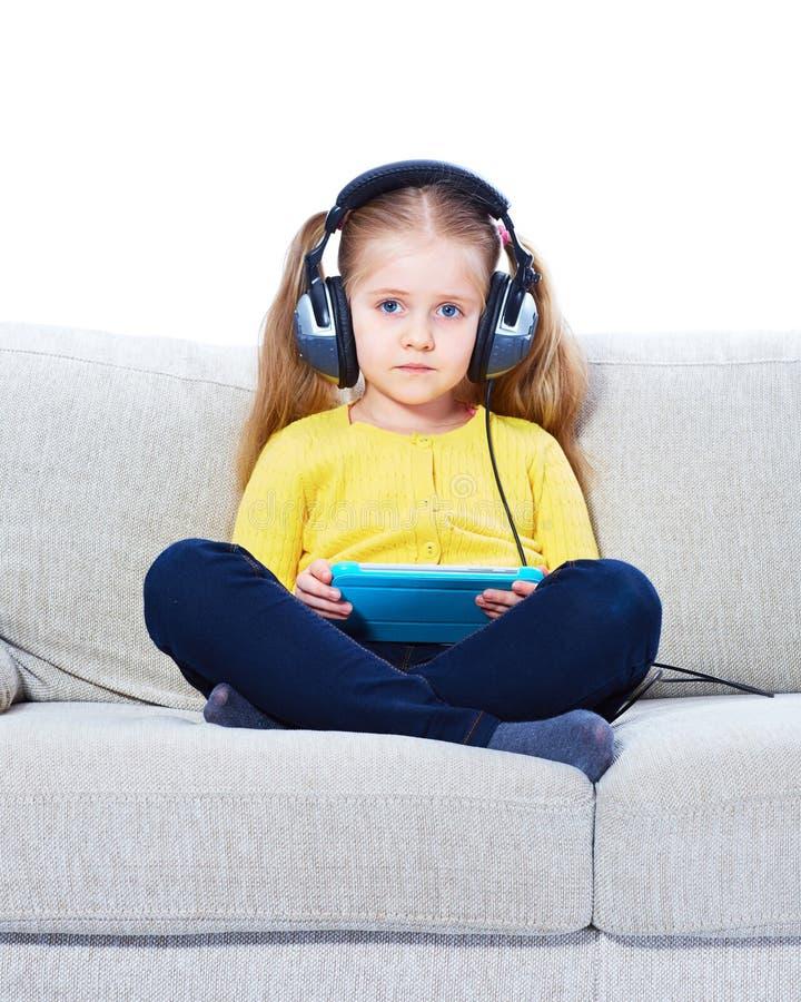 Muchacha que se sienta en el sofá con la tableta imagen de archivo