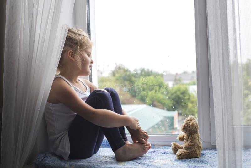 Muchacha que se sienta en el travesaño y las miradas de la ventana hacia fuera la ventana imagenes de archivo