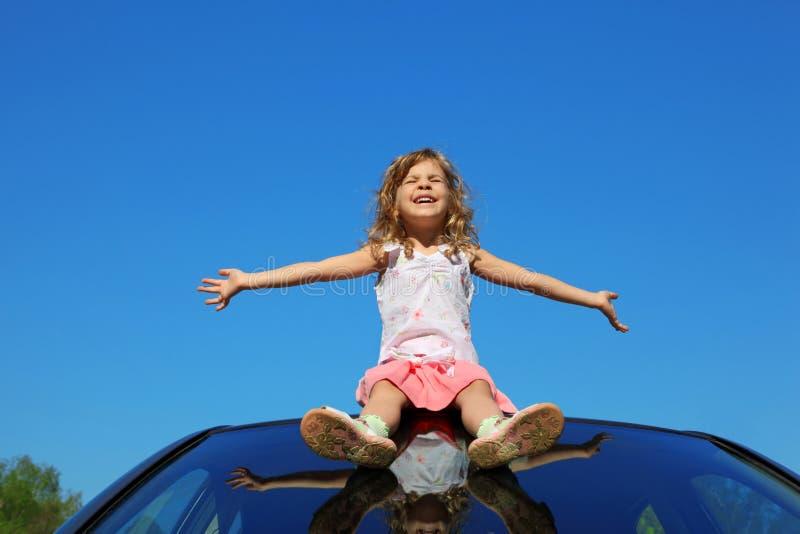 Muchacha que se sienta en la azotea del coche con las manos abiertas imagen de archivo libre de regalías