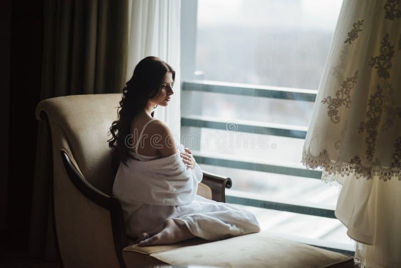 Muchacha que se sienta en la butaca en una posición hermosa imagen de archivo