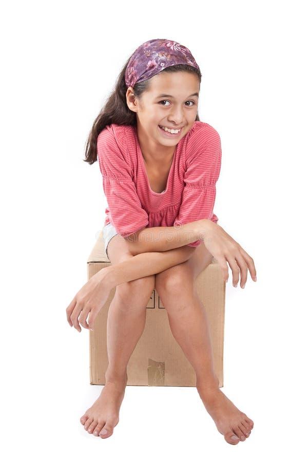 Muchacha que se sienta en la caja de cartón vacía. foto de archivo libre de regalías