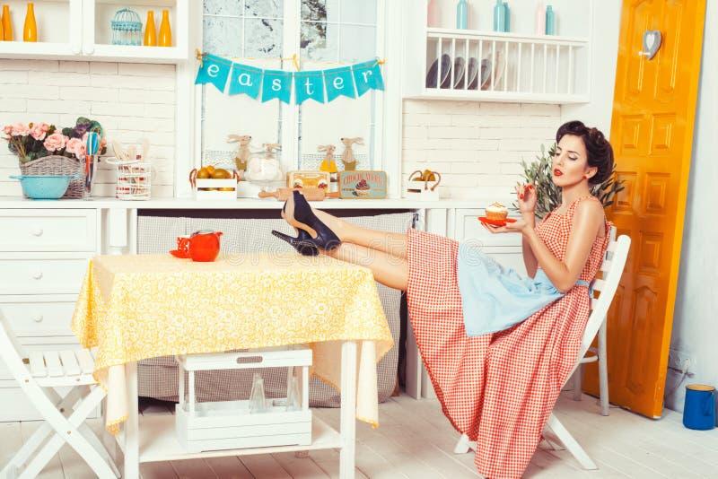 Muchacha que se sienta en la cocina imagen de archivo