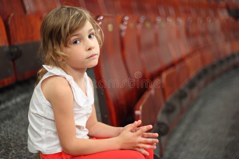 Muchacha que se sienta en la escalera cerca de las butacas en circo foto de archivo libre de regalías
