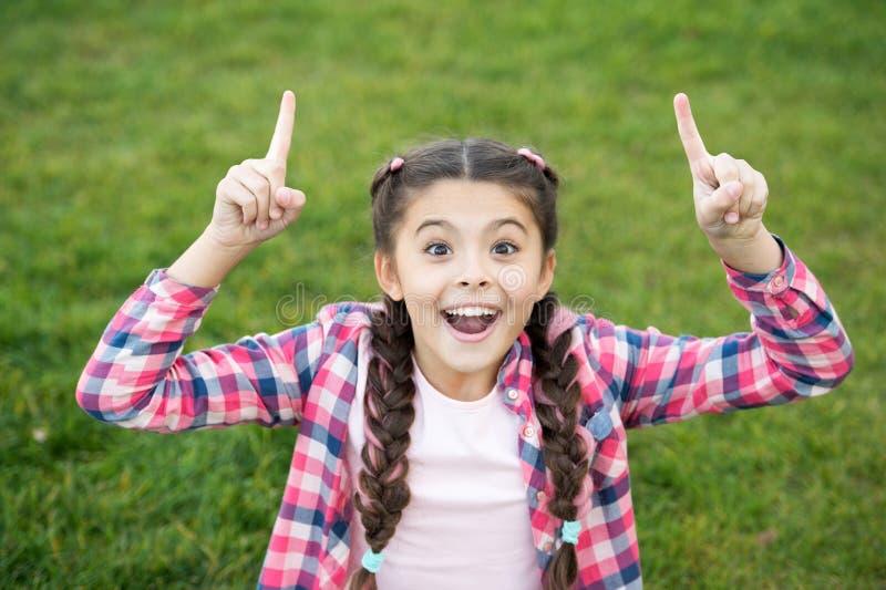 Muchacha que se sienta en la hierba verde clara Pequeña belleza que muestra sus fingeres para arriba Expresión feliz en la cara S fotografía de archivo