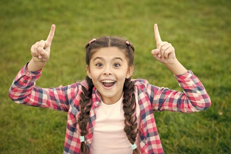 Muchacha que se sienta en la hierba verde clara Peque?a belleza que muestra sus fingeres para arriba Expresi?n feliz en la cara S fotos de archivo libres de regalías