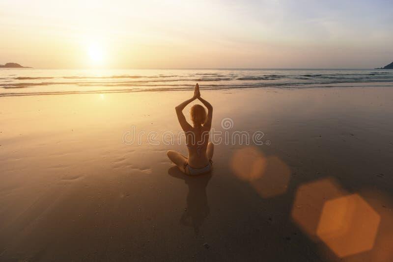 Muchacha que se sienta en la playa durante puesta del sol y que medita en actitud de la yoga imagen de archivo
