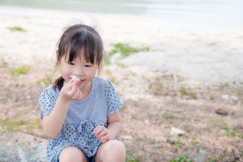 Muchacha que se sienta en la playa, mirando la cáscara y la sonrisa foto de archivo