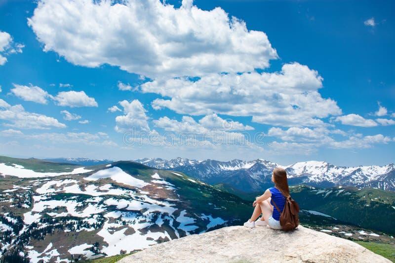 Muchacha que se sienta en la roca en caminar viaje en montañas hermosas foto de archivo libre de regalías