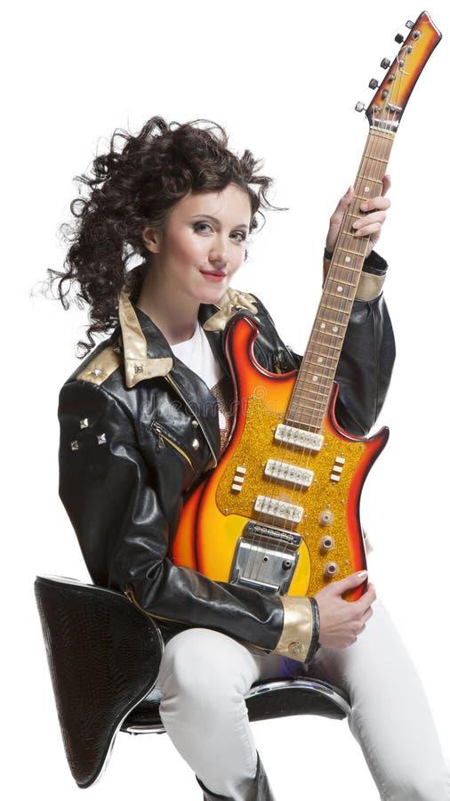 Muchacha que se sienta en la silla con la electro guitarra fotos de archivo