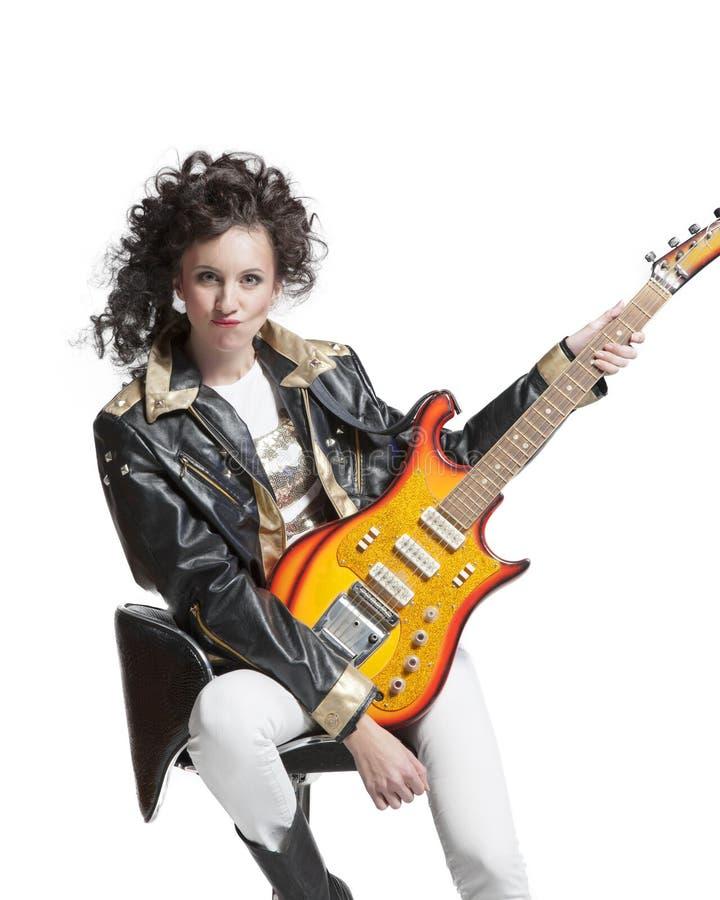 Muchacha que se sienta en la silla con la electro guitarra imagen de archivo libre de regalías