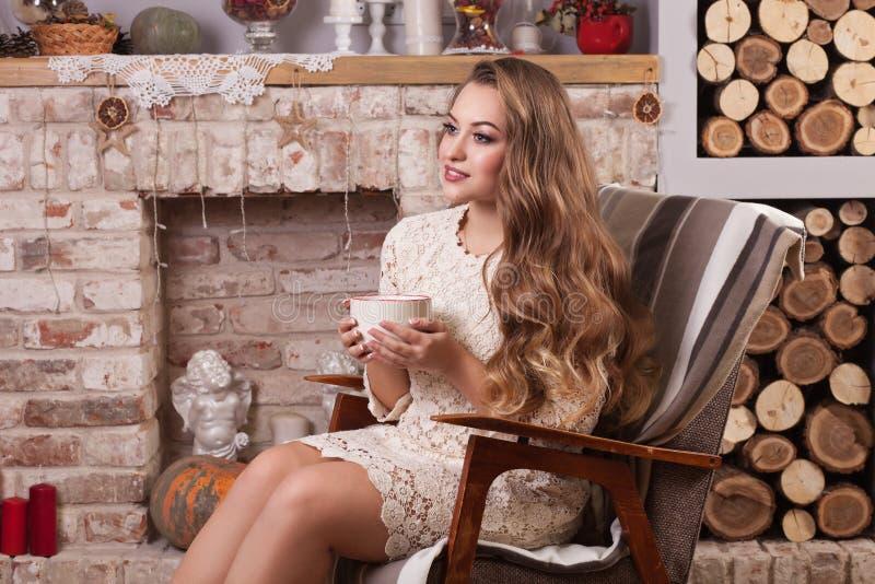 Muchacha que se sienta en la silla y que sostiene la taza con té foto de archivo