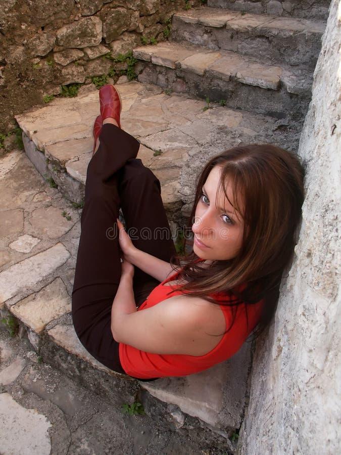 Muchacha que se sienta en las escaleras fotografía de archivo