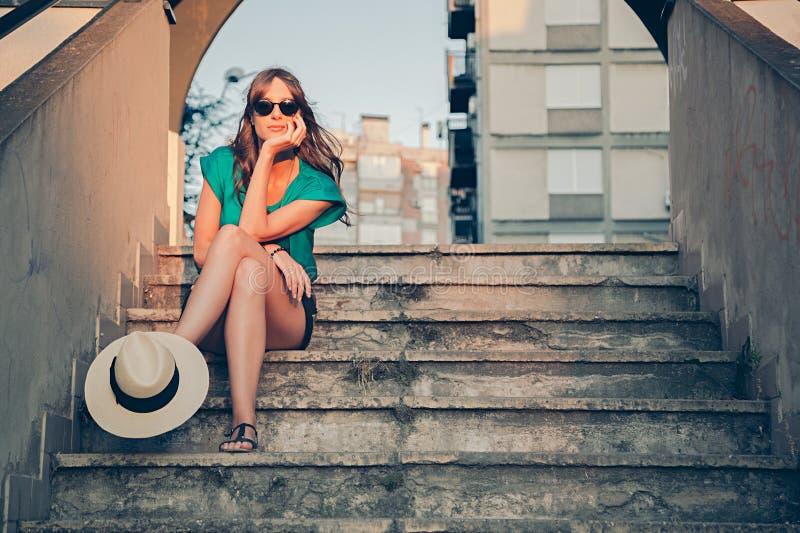 Muchacha que se sienta en las escaleras con el sombrero en su pierna imágenes de archivo libres de regalías