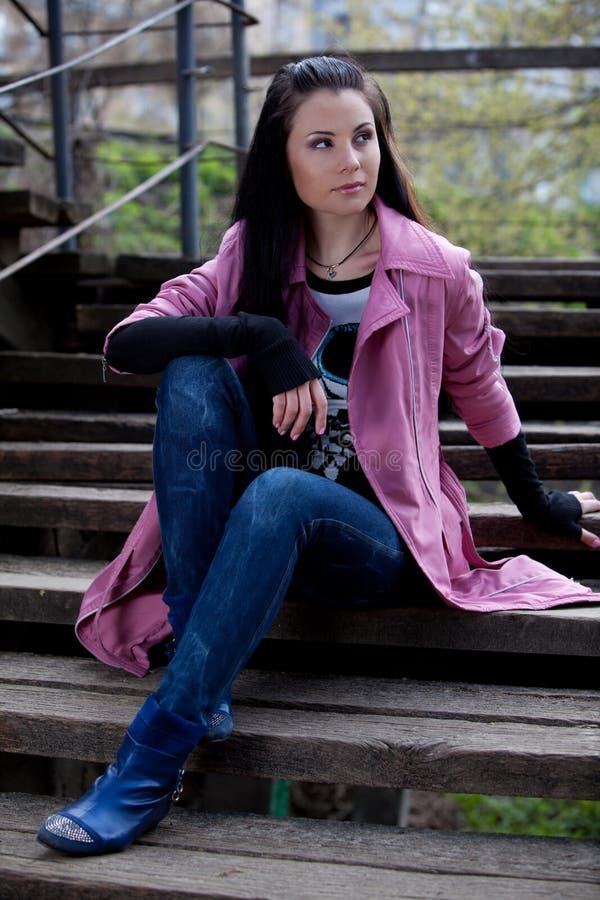 Muchacha que se sienta en las escaleras en el parque imagen de archivo