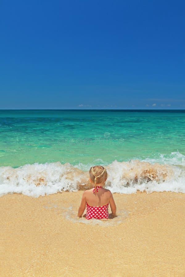 Muchacha que se sienta en las ondas de fractura del océano en la playa de la arena foto de archivo libre de regalías