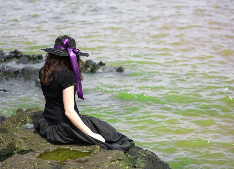 Muchacha que se sienta en las rocas en la costa fotos de archivo libres de regalías