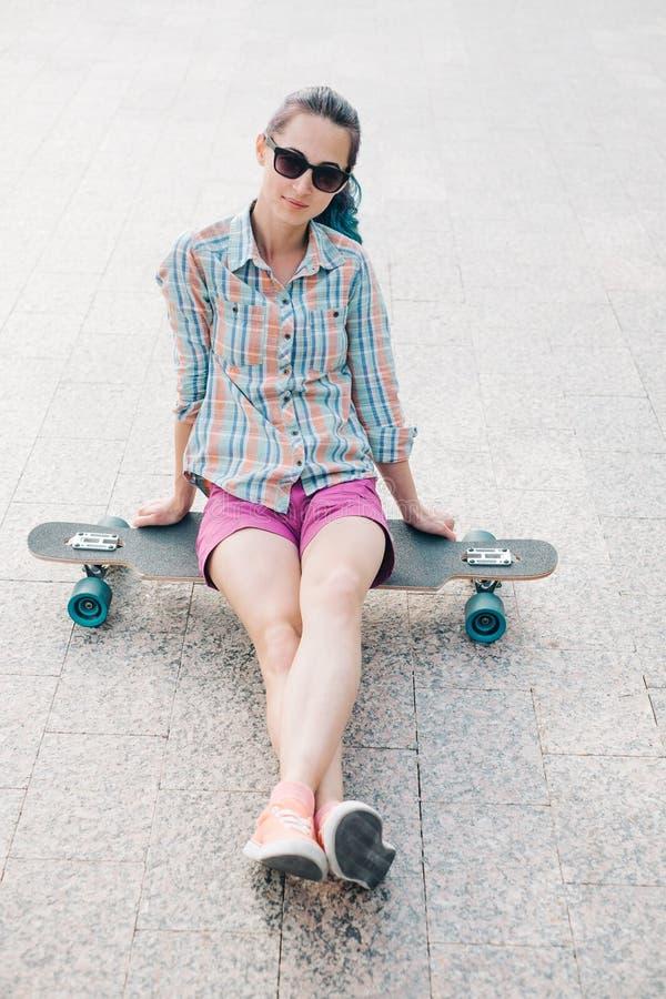 Muchacha que se sienta en longboard imagen de archivo