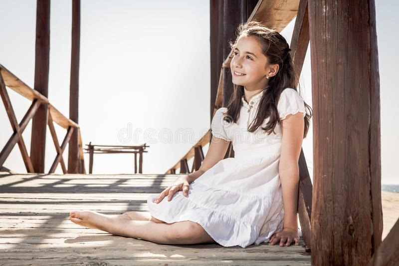 Muchacha que se sienta en piso de madera en la playa imagenes de archivo